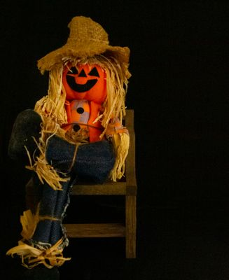 pumpkin head scarecrow sitting in a wooden chair with legs crossed set in a black background.jpg