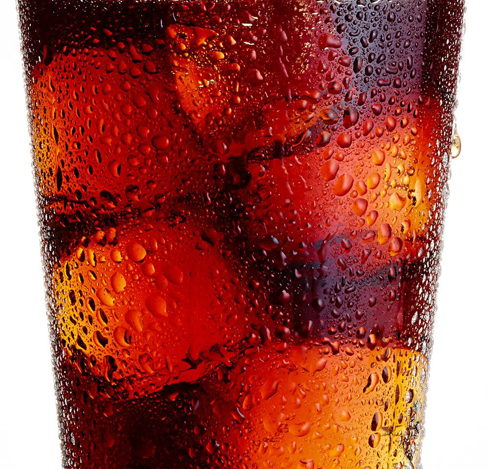 Closeup of a cola drink in a clear glass on ice with condensation and moisture drips on the outside of the glass copy.jpg